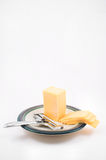 Cheddar Cheese and Slicer. Cheddar cheese and slices on a plate with a cheese slicer Royalty Free Stock Image
