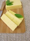 Cheddar cheese slices. On cutting board Royalty Free Stock Photography