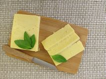 Cheddar cheese slices. On cutting board Royalty Free Stock Image