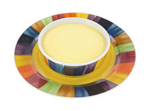 Cheddar cheese soup in bowl on plate Stock Image