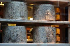 Cheddar Cheese Wheels. Aging Organic Cheddar Cheese Wheels Lying on the Wooden Shelves royalty free stock images
