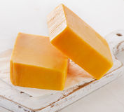 Cheddar Cheese on a white Cutting Board. Royalty Free Stock Photo