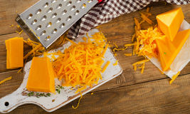 Cheddar Cheese on white cutting Board. Stock Image
