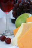 Cheddar cheese with wine and fruit. Yellow and white cheddar cheeses with wine and fruit Stock Photography