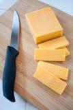 Cheddar-Käse-Block und Scheiben Stockfotos