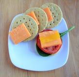 Cheddar-Käse-Block und Scheibentomate pfeffern mit Crackern Lizenzfreies Stockbild