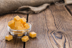 Cheddar. Pieces of Cheddar (close-up shot) on an old wooden table royalty free stock photos