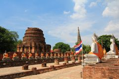 Chedi  and Buddha Images along ruined cloister Royalty Free Stock Photography