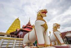 Chedipagoda de oro de Puttakaya con dos el gigante Chinthe en la entrada, distrito de Sangkhlaburi, Kanchanaburi, Tailandia imágenes de archivo libres de regalías