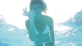 Cheeerful blonde girl in white bikini swims breaststroke and shows OK underwater stock video footage