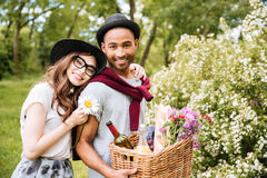 Cheeerful couple with food and drinks for picnic in park Royalty Free Stock Photos