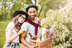 Cheeerful couple with food and drinks for picnic in park Royalty Free Stock Photo