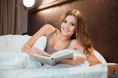 Cheeerful pretty girl reading in bed Royalty Free Stock Photography