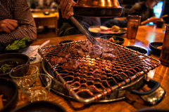 Cheef cooking BBQ beef on fire on guests table in the restaurant Royalty Free Stock Image
