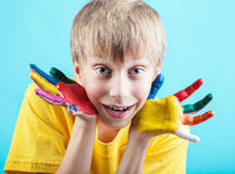 Cheeful boy in yellow t-shirt showing painted hands Stock Images