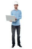 Cheeful builder surfing on his laptop Royalty Free Stock Photo