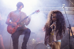 Cheeful female singer with male guitarist performing at nightclub. During music festival Stock Photography