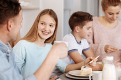 Cheeful girl enjoying dinner with her family. Lovely atmosphere. Cheerful content girl smiling and enjoying dinner with her family while sitting in the kitchen Royalty Free Stock Image