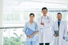 Cheeful hospital workers. Vietnamese hospital workers smiling and looking at camera royalty free stock image