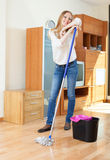 Cheeful long-haired woman washing parquet floor. With mop in living room Royalty Free Stock Photography