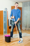 Cheeful man washing parquet floor with mop Stock Photography