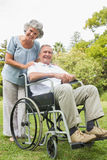 Cheeful mature man in wheelchair with partner Stock Photos