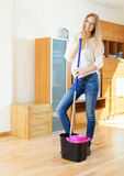 Cheeful ordinary woman washing parquet  with mop. Cheeful ordinary woman washing parquet floor with mop in living room Stock Photos