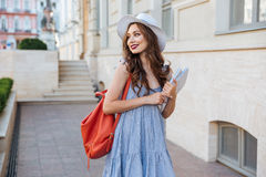 Cheeful woman with backpack and book walking in the city Stock Photos