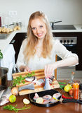 Cheeful woman putting pieces of fish in frying pan Stock Image