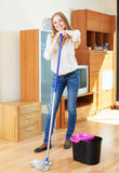 Cheeful woman washing parquet floor with mop Stock Photography