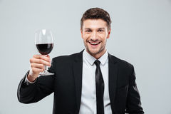 Cheeful young businessman smiling and drinking red wine Stock Photo