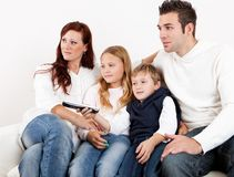 Cheeful young family watching TV at home Stock Images