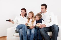 Cheeful young family watching TV at home. Cheeful young family watching TV together at home Royalty Free Stock Photography