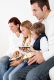 Cheeful young family watching TV at home Stock Photos