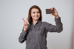 Cheeful young lady make selfie by mobile phone. Royalty Free Stock Images