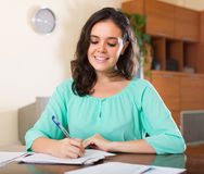Cheeful young woman reading documents Royalty Free Stock Photo