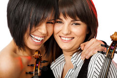 Cheek to cheek smiling violinists. Two beautiful girls cheek-to-cheek smiling and hugging holding violins Royalty Free Stock Photos