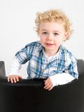 Cheeky Boy. A young boy posing on a chair stock photo