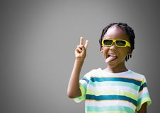 Cheeky Boy against grey background with sunglasses sticking out tongue royalty free stock photos