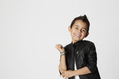Cheeky boy in leather jacket. Boy in leather jacket with cheeky smile in studio Stock Photography
