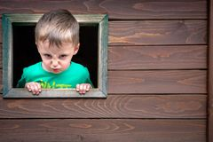 Cheeky boy looking through the window. Portrait of a cute cheeky little Caucasian boy looking through the window of a wooden toy house in a outdoor playground royalty free stock photos