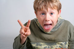 Cheeky boy making funny face. A portrait of a cheeky young boy, sticking his tongue out and making the peace sign with his fingers royalty free stock image