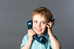 Cheeky boy talking on both ears for two voices communication Royalty Free Stock Images