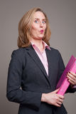 Cheeky businesswoman with pink folder. Businesswoman with cheeky expression carrying pink folder royalty free stock photo