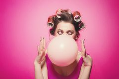 Cheeky girl with bubble gum posing on pink background in body, with curlers on head. Pretty woman with sweet makeup making. Balloons with bubblegum in studio royalty free stock images
