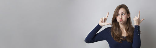 Cheeky girl enjoying an exaggerated LOL with a funny face. Cheeky young girl making the LOL sign with exaggeration, humor for boring trends in hand gesture, long Stock Image