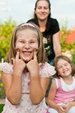 Cheeky girl - grimace. Child with cheeke expression - mother and sister in background Royalty Free Stock Photography