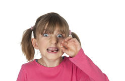 Cheeky girl holding missing tooth Royalty Free Stock Image