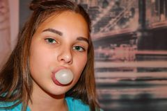 The cheeky girl is a teenager. Portrait of a modern girl with an impudent look. Long fair-haired hair, green eyes. In the mouth a bubble of chewing gum. The Royalty Free Stock Photography
