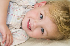 Cheeky Grin. A young blond boy laying down and giving a cheeky grin Stock Photo
